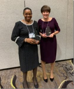 Two Women holding awards