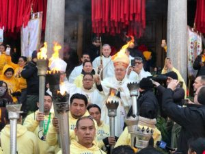 Bishop holding up torches with men