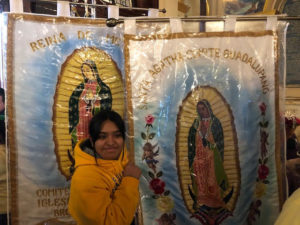Girl taking a picture with Our Lady of Guadalupe poster